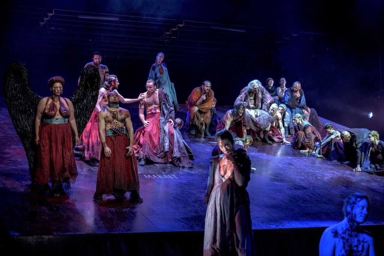 Grupa ludzi, większa ich część stoi albo siedzi na podnoszonej płaszczyźnie sceny. Na środku znajduje się Makbet, obok niego Banquo, z lewej strony stoi półnaga Hekate, z dużymi, czarnymi skrzydłami. Na pierwszym planie jedna z wiedźm. Wszyscy mają zniszczone, przybrudzone, zakrwawione szaty.