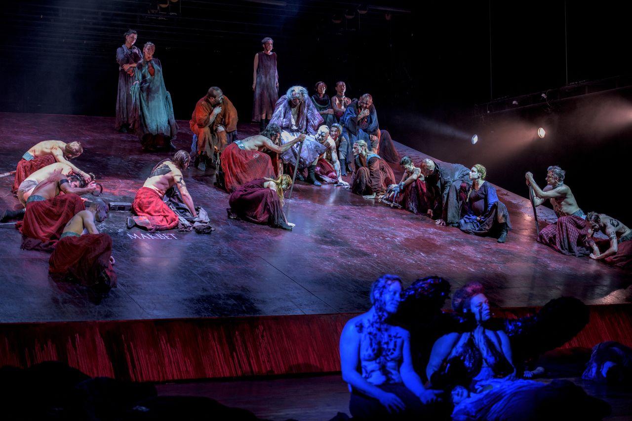 Grupa ludzi, prawie wszyscy stoją albo siedzą na podnoszonej płaszczyźnie sceny. Na pierwszym planie, w niebieskim świetle siedzą Hekate i Lulach. Niektórzy są półnago, większość ma zniszczone, przybrudzone, zakrwawione szaty.