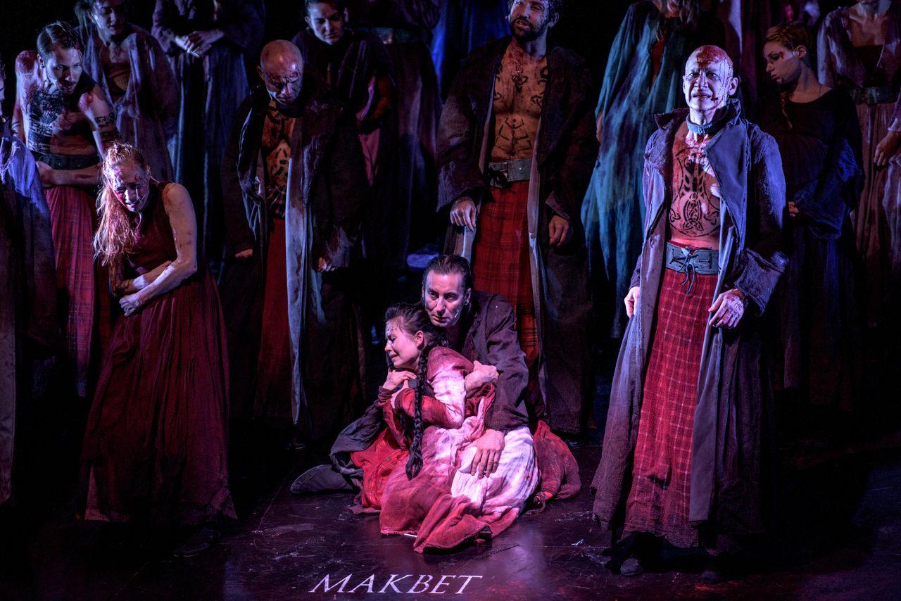 Grupa ludzi, mężczyzn i kobiet. Na pierwszym planie, na środku siedzi Makbet i przytula przywierającą do niego bokiem ciała, Lady Makbet. Z prawej strony stoi, wysoki, łysy, wytatuowany mężczyzna, w płaszczu nałożonym na goły tors i w szkockiej, długiej, spódnicy. Wszyscy są zakrwawieni i sponiewierani.