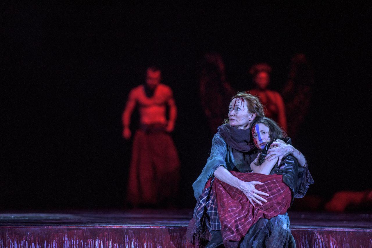 Na brzegu zakrwawionej sceny siedzi kobieta trzymająca w objęciach nastoletnie dziecko. Zwraca z niepokojem twarz ku zbliżającym się z tyłu, złowrogim, zalanym czerwonym światłem postaciom. Jedną z nich jest Hekate.