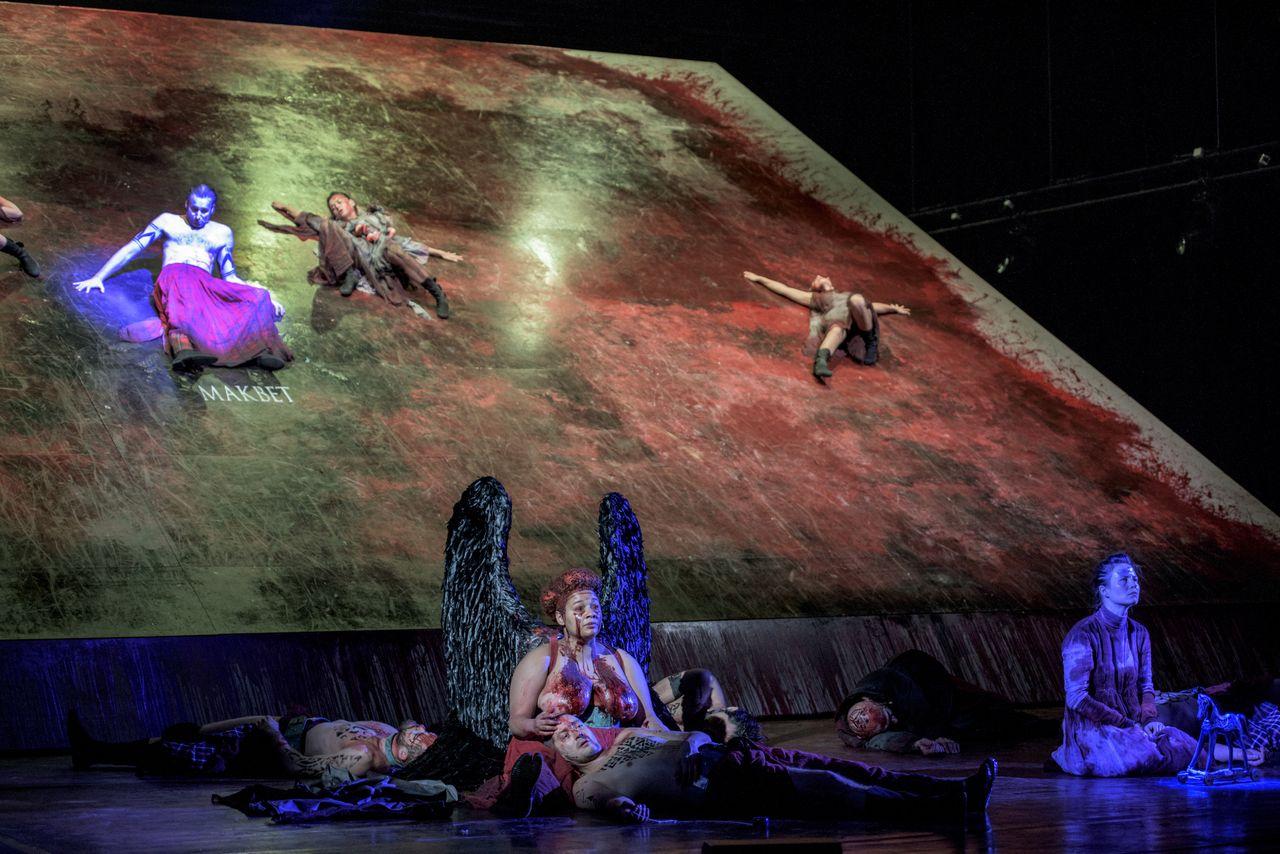 Kilka postaci siedzi i leży na podnoszonej płaszczyźnie sceny tworzącej niemal pionową ścianę. Są to Makbet i wiedźmy, zsuwający się w dół, ku siedzącym tam Hekate i Lady Makbet. Na dole widać też leżących ludzi.