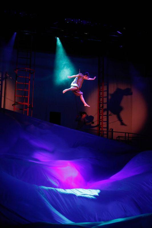 Dorotka leci w powietrzu, oświetlona postać unosi się w ciemnej przestrzeni ponad niebieską i fioletową płaszczyzną.