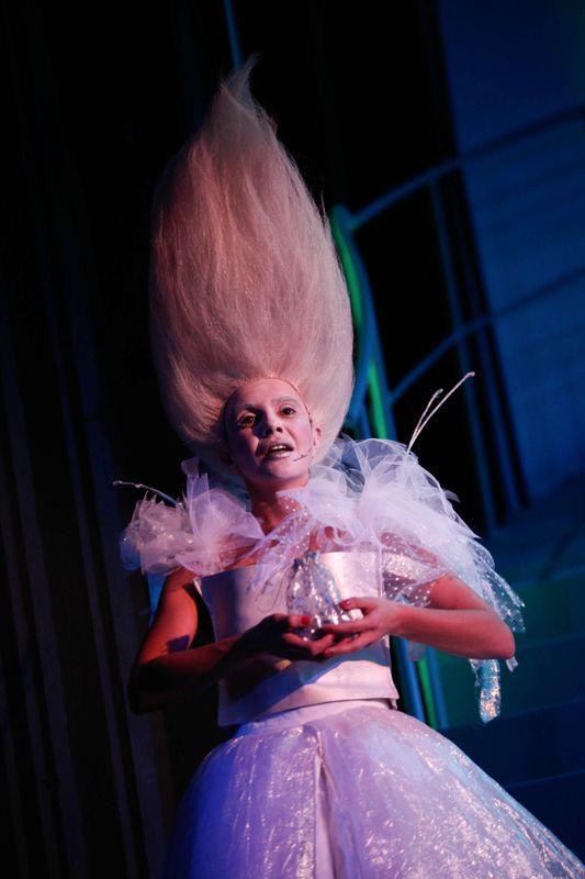 Postać Szeleszczącej. Cała w bieli, z białą twarzą i białymi, długimi włosami , ułożonymi wysoko do góry.