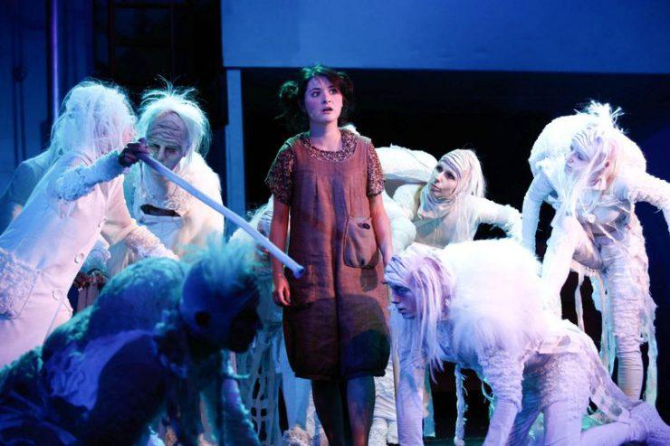 Dorotka stoi w centrum, otoczona białymi, dziwnymi postaciami.
