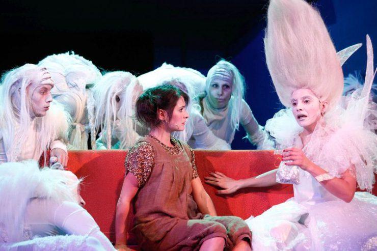Ubrana na brązowo Dorotka siedzi na czerwonej kanapie, słucha Szeleszczącej, całej w bieli. W tle białe postacie.