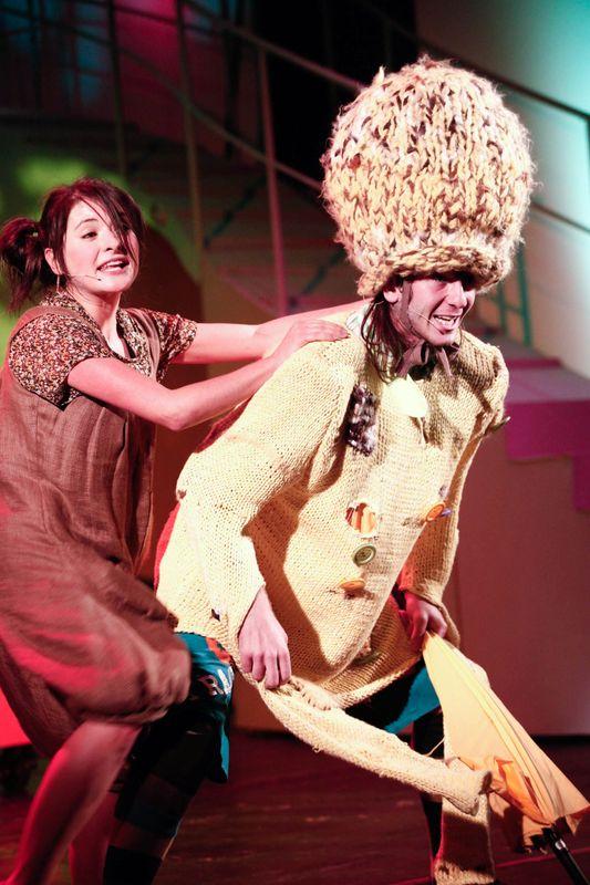 Dorotka z lewej strony, trzyma dłonie na ramionach Stracha Na Wróble, ubranego w połatany, jasny płaszcz.