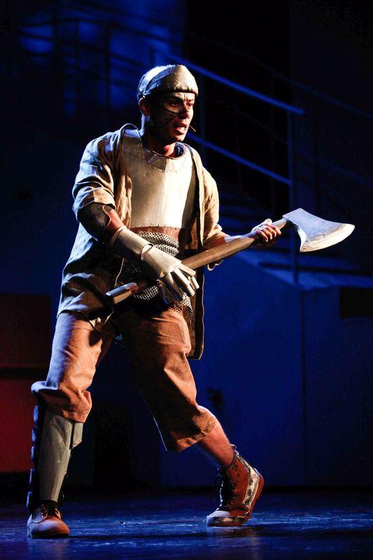 Blaszany Drwal w beżowym, brązowym i szarym stroju imitującym blachę, trzyma w obydwu dłoniach siekierę.