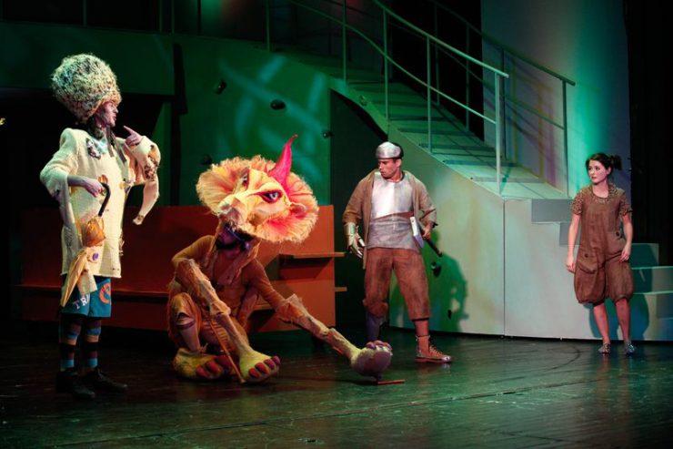 Czworo postaci na tle konstrukcji ze schodami. Od lewej: Strach na Wróble, Tchórzliwy Lew, Blaszany Drwal i Dorotka.