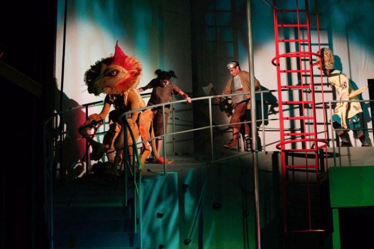 Na wyższej konstrukcji ze schodami idą, od lewej: Tchórzliwy Lew, Dorotka, Blaszany Drwal i Strach na Wróble.