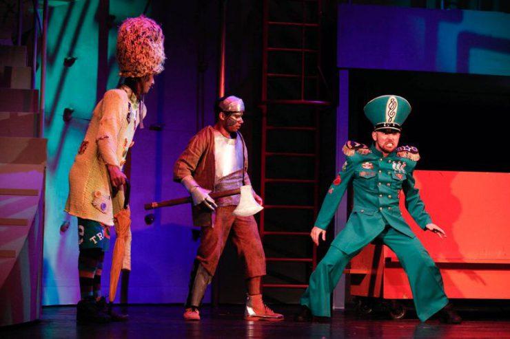 Strach na Wróble i Blaszany Drwal patrzą na Strażnika w zielonym mundurze i wysokiej czapce, stojącego z prawej strony.