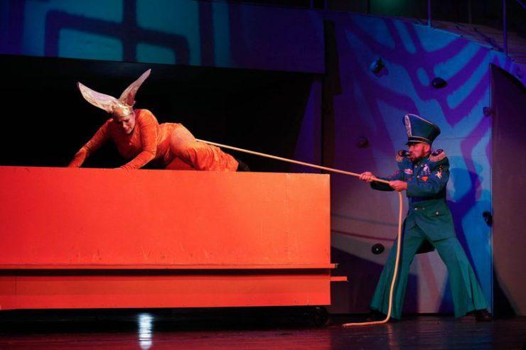 Z lewej strony, na czerwonym postumencie leży Królowa Myszy, za długi ogon ciągnie ją, stojący po prawej, Strażnik.