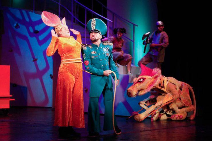 Wystraszona Królowa Myszy stoi z prawej, obok – groźny Strażnik, w tle z lewej strony: Lew, Dorotka i Drwal.