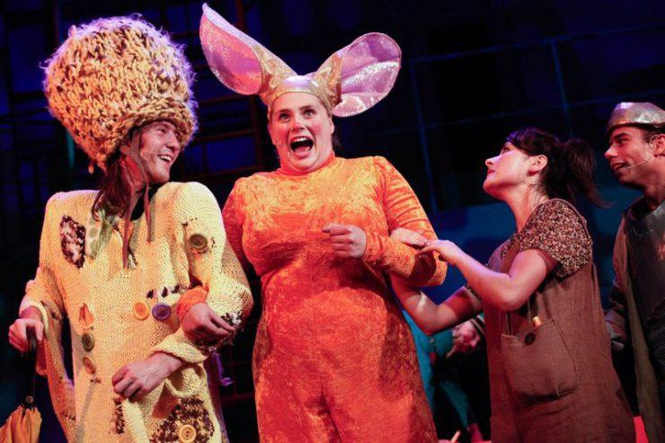 Od lewej strony uśmiechnięty Strach, obok śpiewającej Królowej Myszy, przy której stoją i patrzą na nią Dorotka oraz Drwal.