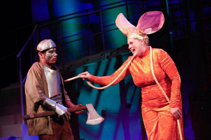 Z lewej strony Blaszany Drwal, z prawej – Królowa Myszy, która dotyka go w ramię sznurem-ogonem.