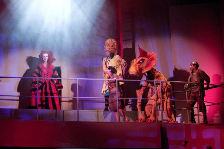 Metalowa barierka, za nią w głębi, z lewej strony – złowroga postać kobiety w czerwono-czarnej sukni i masce, z prawej patrzą na nią: Dorotka, Strach na Wróble, Lew i Drwal.