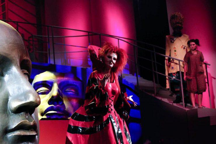 Z lewej strony makieta ogromnej twarzy, na środku – postać kobieca w masce i czerwono-czarnej sukni, w tle, wyżej, z prawej strony patrzą na nią Dorotka i Strach na Wróble.