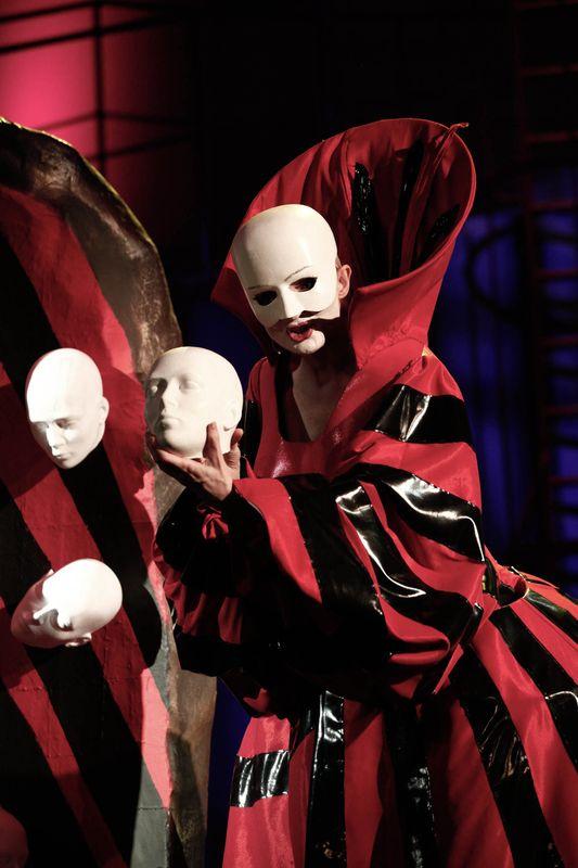 Bezgłowa, w masce, bez włosów i w czerwono-czarnej sukni, trzyma w dłoniach białą, bezwłosą atrapę głowy, z lewej strony dwie takie głowy są elementami scenografii.