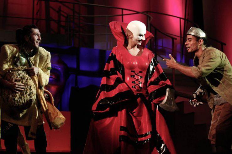 Z lewej strony Strach na Wróble, trzyma swoją ogromną czapę, na środku Bezgłowa w masce i czerwono-czarnej sukni, z prawej Blaszany Drwal, który coś do niej mówi.