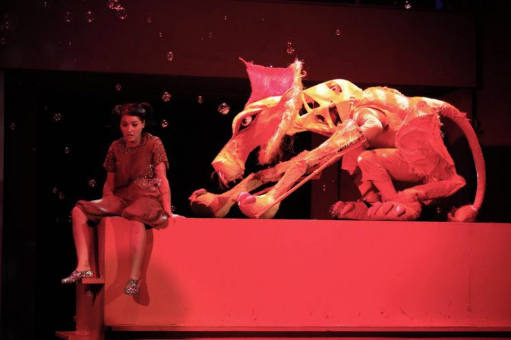 Czerwony, długi postument, z lewej jego strony siedzi Dorotka, ma na stopach błyszczące buciki, z prawej strony przysiada Tchórzliwy Lew.