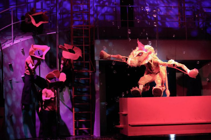 Na czerwonym postumencie stoi Lew, spadają na niego z góry bańki mydlane, patrzy na postaci – kwiaty maku, znajdujące się z lewej strony.