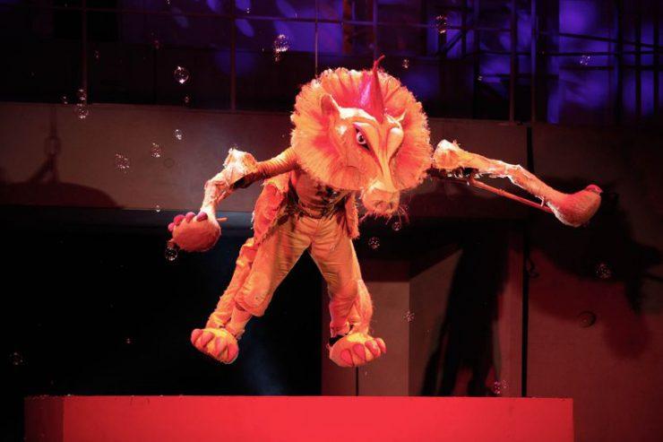 Tchórzliwy Lew zawieszony w powietrzu nad czerwonym postumentem, spadają na niego bańki mydlane.