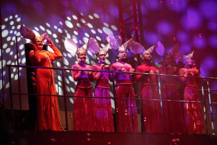 Na platformie, za barierką, stoją od lewej: Królowa Myszy i sześć Myszy w rzędzie, z dużymi uszami, ubranych identycznie w pomarańczowe stroje. Spadają na nich bańki mydlane