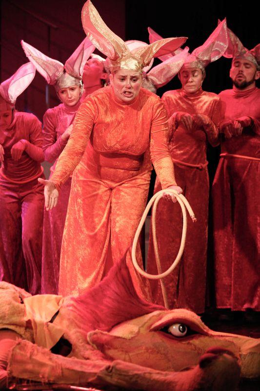Królowa Myszy stoi z rozłożonymi rękami nad leżącym Tchórzliwym Lwem, w tle kilka Myszy w rzędzie.