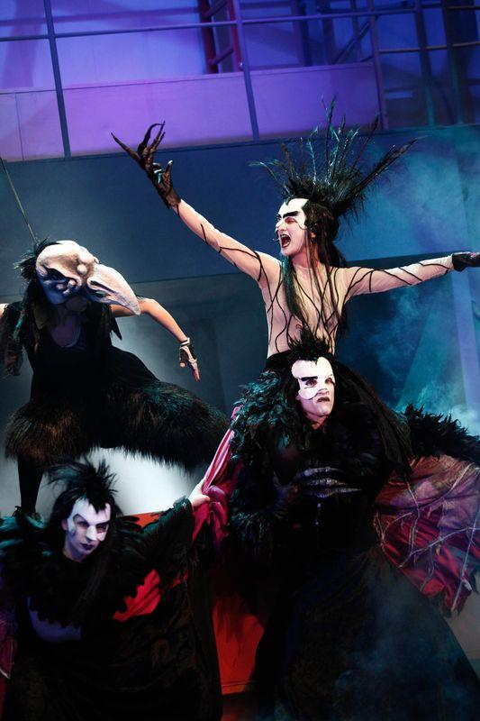 Wroniasta siedzi na Wronie. Obok i z tyłu także Wrony. Postaci w kostiumach z czarnymi piórami, w białych maskach, z czarnymi rękawiczkami ze szponami.