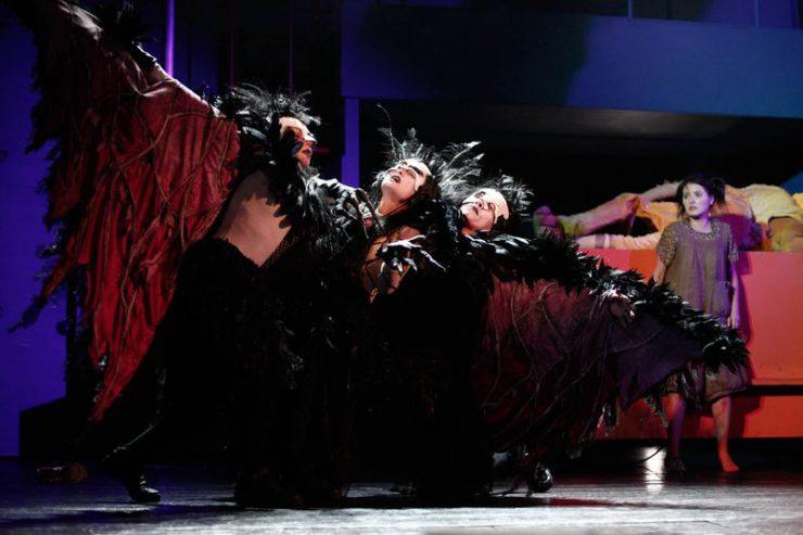 Wroniasta pomiędzy dwiema Wronami z rozłożonymi skrzydłami. Kostiumy czarne i czerwone, z piórami, na twarzach maski. Wronom przygląda się stojąca w tle z prawej strony Dorotka.