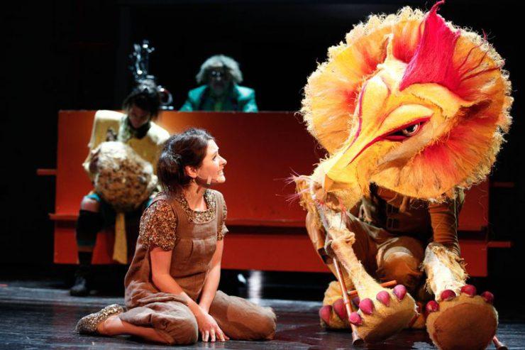Z lewej strony siedzi Dorotka, rozmawia z Lwem. W tle widać Stracha na Wróble i Oza.