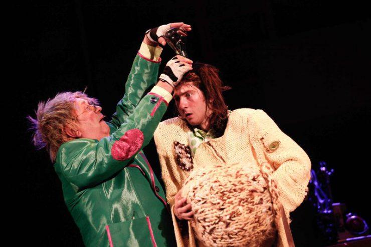 Rozczochrany Oz trzyma w dłoniach, nad głową Stracha na Wróble, metalowe urządzenie.