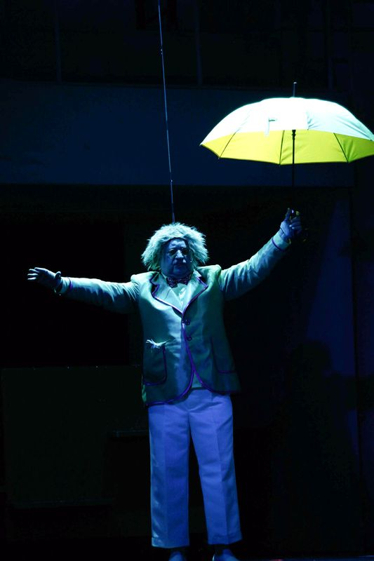 Rozczochrany Oz stoi w niebieskiej poświacie, z rozłożonymi na boki rękami, w lewej dłoni ma otwarty parasol, wygląda jakby miał unieść się w górę.