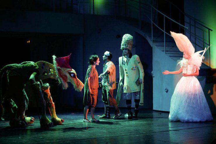 Przy konstrukcji ze schodami, stoją w niebiesko-zielonym świetle, od lewej: Lew, Dorotka, Drwal, Strach i Szeleszcząca w białej sukni.