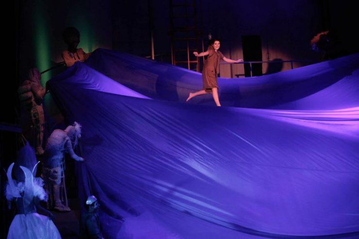 Dorotka unosi się nad dużą, fioletową, falującą płaszczyzną, z lewej strony widoczne inne postaci.