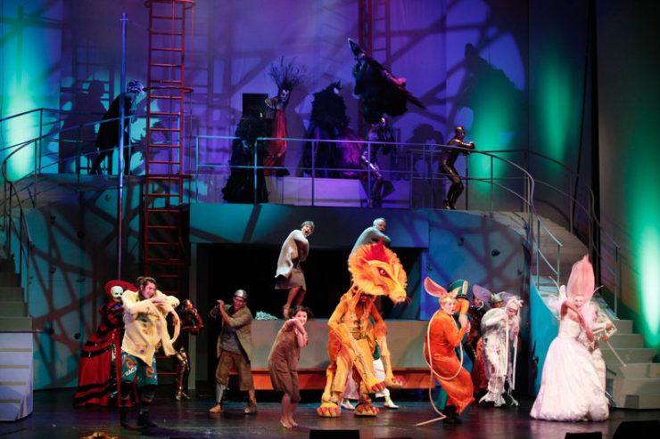 Scena zbiorowa z wysoką konstrukcją ze schodami w tle. Z przodu jasno oświetleni śpiewający i tańczący główni bohaterowie, wyżej na platformie kilka ciemnych postaci.