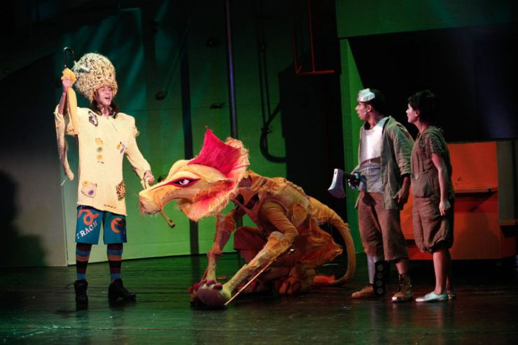 Z lewej strony stoi Strach na Wróble z wyciągniętą do góry prawą dłonią, w której trzyma złożony parasol. Na środku siedzi lew, z prawej srony stoją Blaszany Drwal i Dorotka.