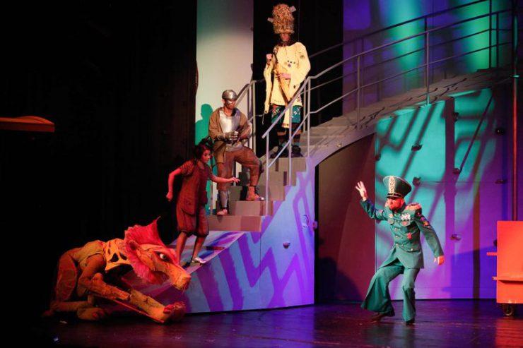 Na schodach z lewej strony stoją, od dołu: Lew, Dorotka, Blaszany Drwal i Strach na Wróble. Z prawej strony znajduje się umundurowany Strażnik z wyciągniętą ku górze, prawą dłonią.