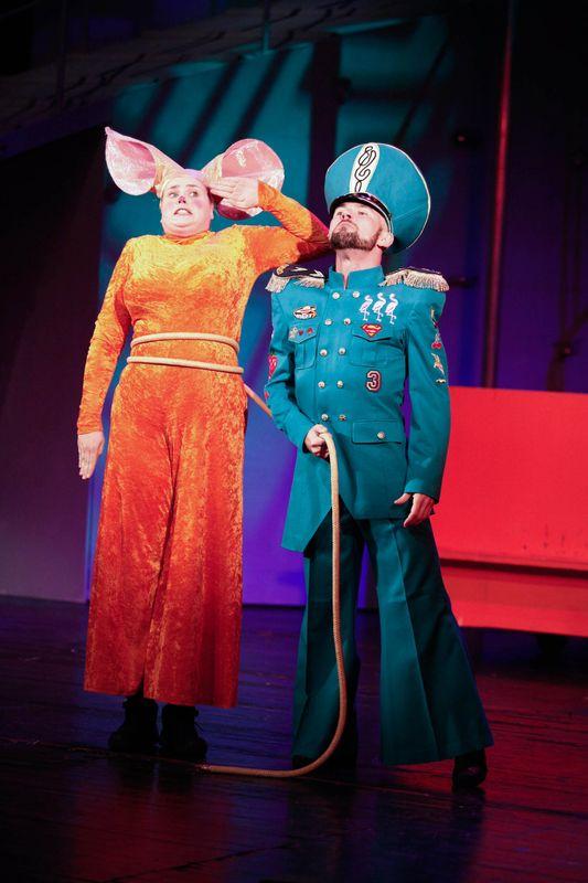 Z lewej strony stoi Królowa Mysz, ma przestraszoną twarz, salutuje. Obok niej, trzymając za sznur-ogon, stoi umundurowany Strażnik.