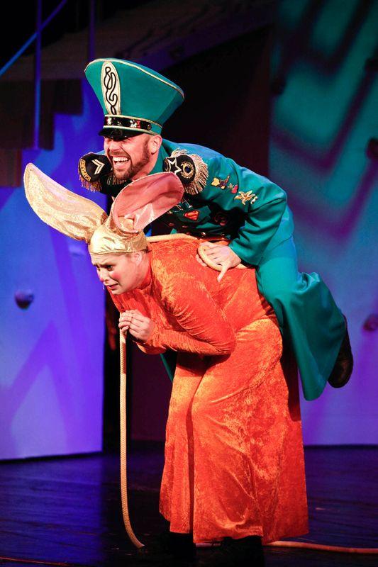 Pochylona, wystraszona Królowa Mysz, ze złożonymi u góry dłońmi, na niej siedzi z tyłu, przechylony w przód, wyszczerzony Strażnik w zielonym mundurze.