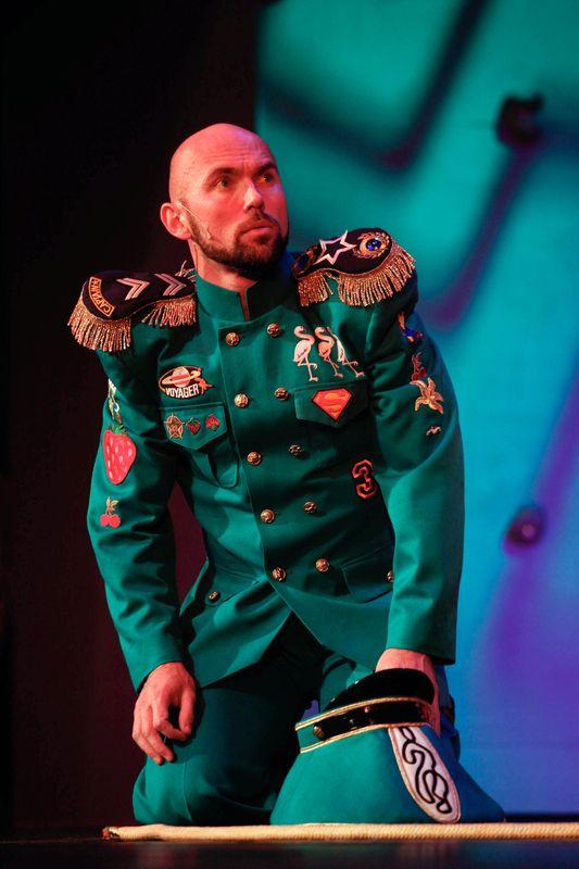 Strażnik w zielonym mundurze, obszytym wieloma kolorowymi naszywkami, siedzi na kolanach, obok jego lewej nogi leży czapka.