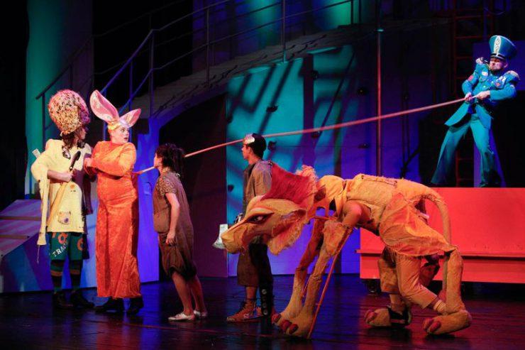 Od lewej strony stoją: Strach na Wróble, Królowa Mysz, Dorotka, Blaszany Drwa i Tchórzliwy Lew. Za nimi stoi na czerwonym postumencie Strażnik, trzyma za sznur-ogon Królowej Myszy.