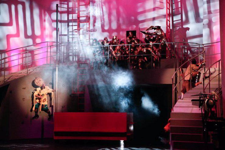 Konstrukcja z barierką i wysokimi schodami, u góry stoją na niej w grupie Kalidachy w metalicznych, miedzianych kostiumach, na dole, z lewej strony widoczny Strach na Wróble.