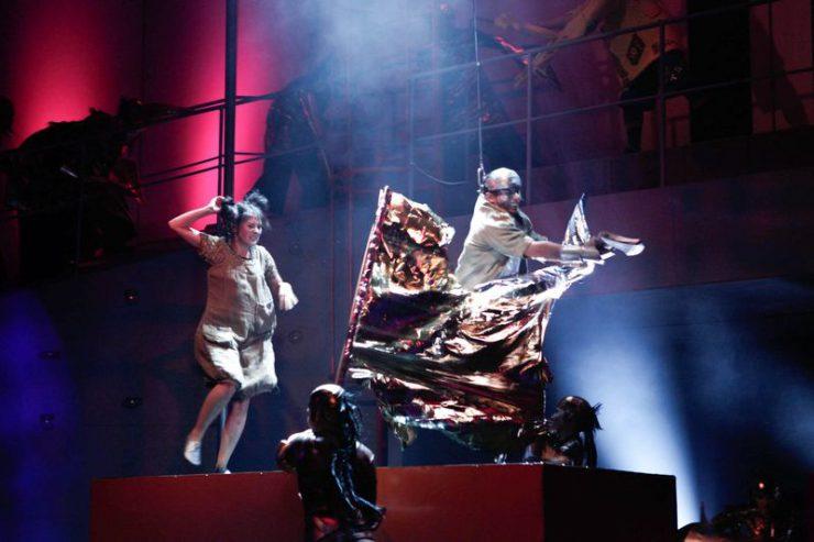 Dorotka na podwyższeniu z lewej strony, przed nią Blaszany Drwal uderzający siekierą w metaliczną zasłonę, przytrzymywaną u dołu przez Kalidachy.