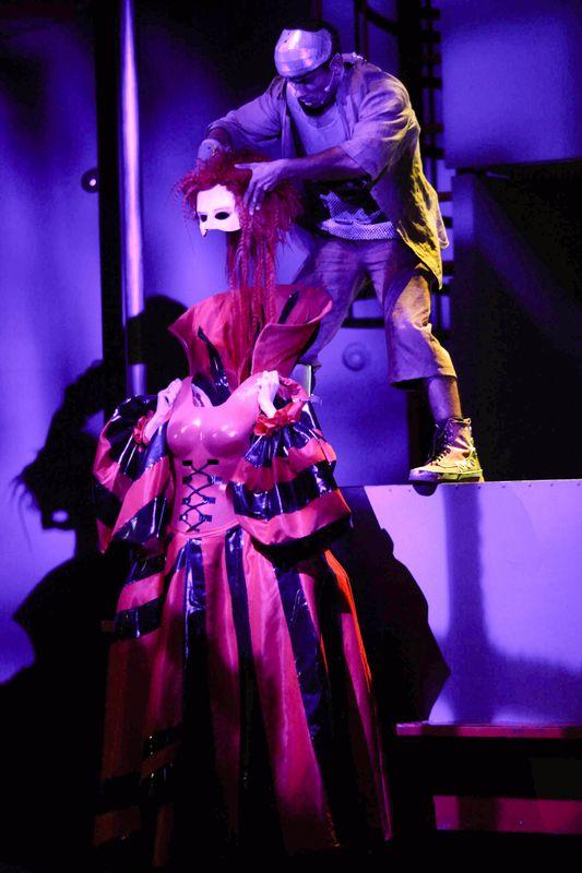 Blaszany Drwal stoi na podwyższeniu, nad bezgłową postacią w czerwono-fioletowej długiej sukni. Drwal trzyma białą maskę z długimi włosami.
