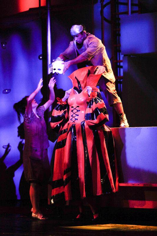 Blaszany Drwal stoi na podwyższeniu, nad bezgłową postacią w czerwono-fioletowej długiej sukni. Drwal podaje stojącej z lewej strony Dorotce, białą maskę z długimi włosami.