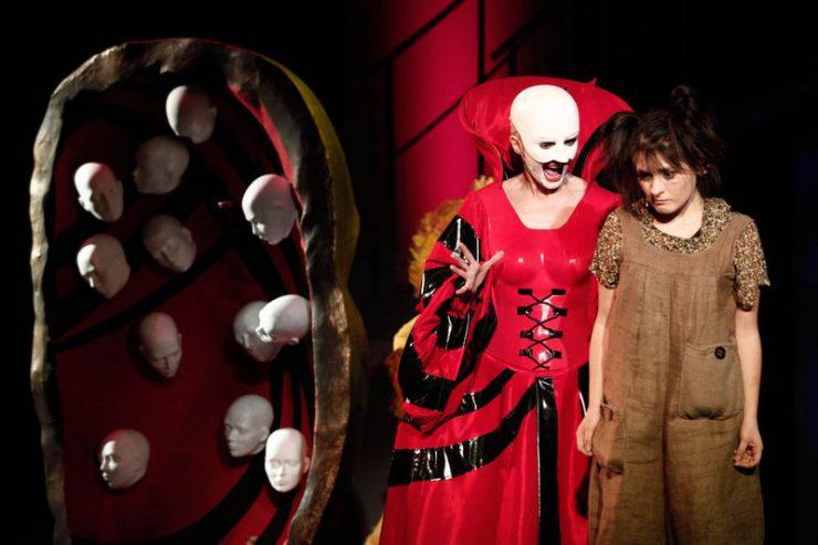Z prawej strony stoi Bezgłowa, w białej masce bez włosów i czerwono-czarnej sukni. Gestykuluje i mówi coś do stojącej obok Dorotki. Z lewej strony scenografia z białymi, bezwłosymi głowami.