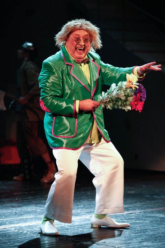 Śpiewający, rozczochrany Oz ma okulary, zieloną marynarkę, jasne spodnie, w prawej dłoni trzyma sztuczny kwiat.
