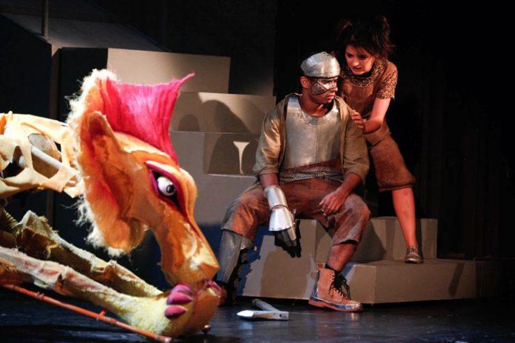 Na schodkach siedzi Blaszany Drwal, nad nim Dorotka, zwrócona w stronę Drwala i mówiąca coś do niego. Z lewej strony widać Lwa.