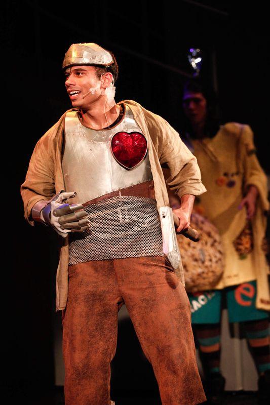 Blaszany Drwal trzyma w lewej ręce siekierę. Beżowy, srebrny i brązowy kostium Drwala ożywia szkarłatne, duże serce. W tle widać Stracha na Wróble.