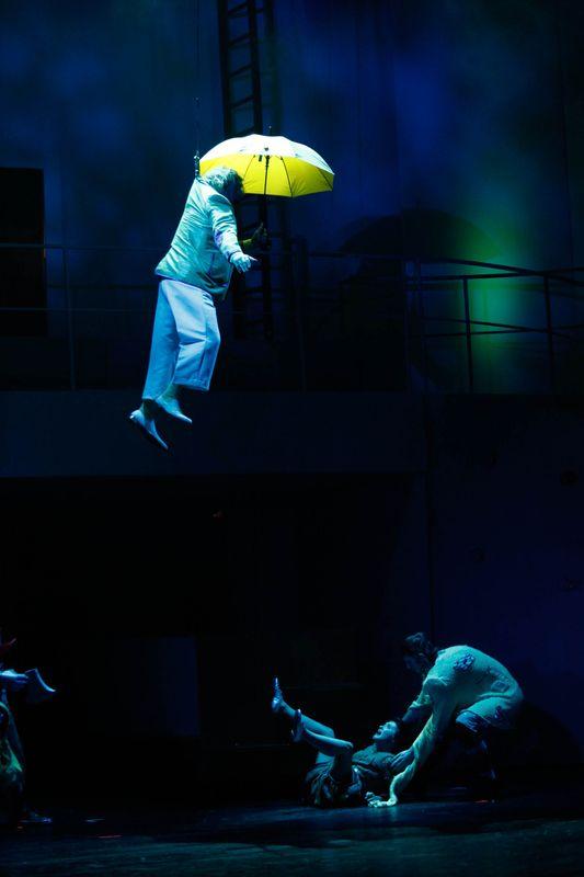 Zaciemniona scena, u góry unosi się Oz z rozłożonym parasolem, poniżej leży Dorotka, podtrzymywana przez Stracha na Wróble.